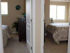 A hallway view of two bedrooms in a townhome.