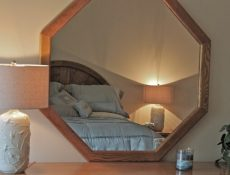 View of a bedroom through a mirror hanging on the wall.